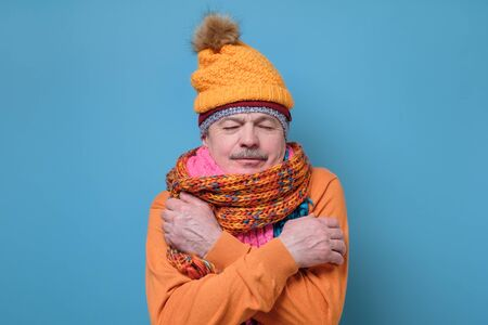 Senior man wearing several hats and scarfs freezing because of cold weather.