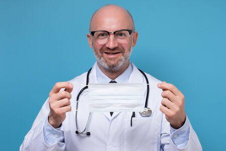Doctor wearing medical face mask for corona virus, studio portrait. 免版税图像