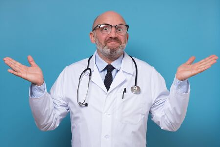 Mature male doctor shrugging lifting shoulders having no idea how to cure