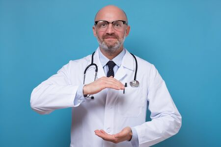 Handsome mature doctor holding something big between hands with copyspace