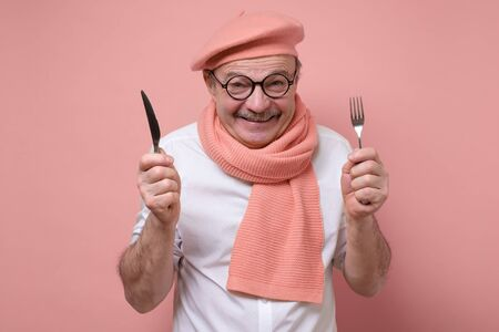 Hungry excited hispanic senior man holding fork and knife on hand ready to eat.
