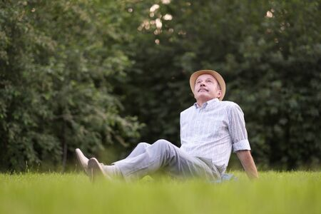 Elderly spanish man resting, on fresh air lying on ground looking up.