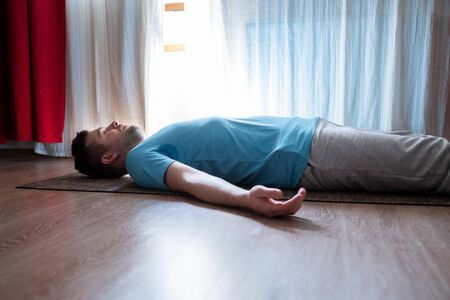 Young man meditating on a floor and lying in Shavasana pose at his living room. Imagens