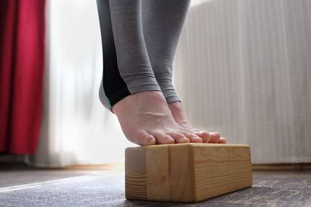 Woman doing exercise for strong foot using wooden props.