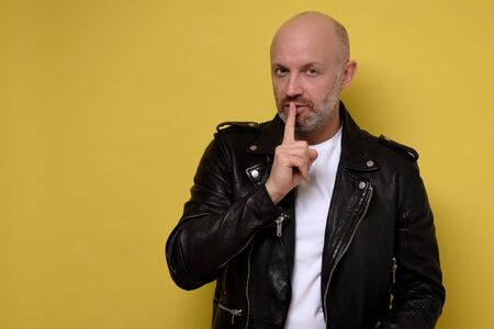 Serious italian man keeps fore finger on lips, tries to keep conspiracy.