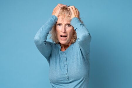 Mature woman holding head in hands feels unhealthy
