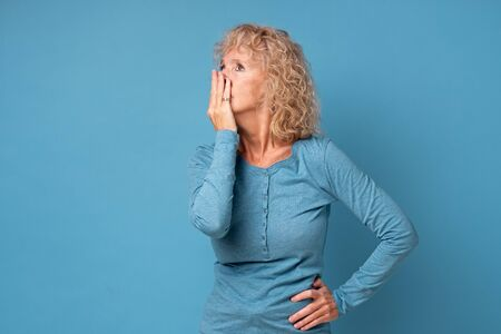 Scared middle aged senior woman covering mouth with hands feel horrified, stunned old blond female received shocking news. Studio shot on blue wall.