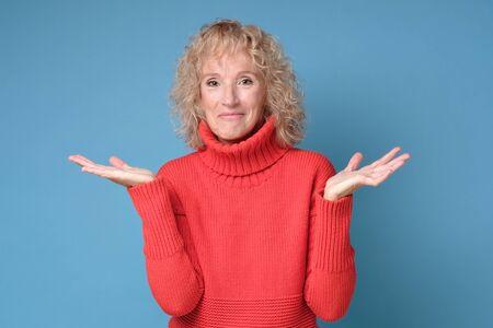 Doubtful mature woman shrugs shoulders having no idea what to do