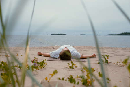 Young man doing yoga on a lake on a summer day, meditation, relaxation pose, Shavasana or dead man asana