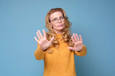 Stressed out angry mature woman keeping hands in stop gesture