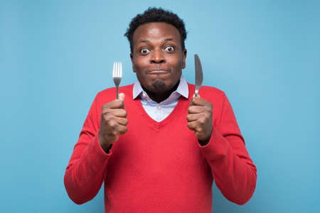 Hungry african man holding fork and knife raised waiting for dinner. Stock Photo