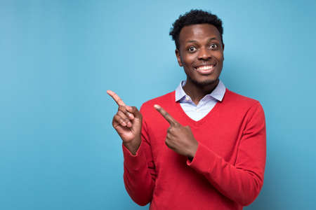 Amazed african man student pointing finger aside at copy space