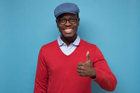 african man with cheerful facial emotion showing thumb up