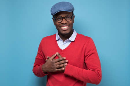 African cheerful man smiles happily, keeps hands on chest, recieve compliment from woman. Studio shot on blue wall.