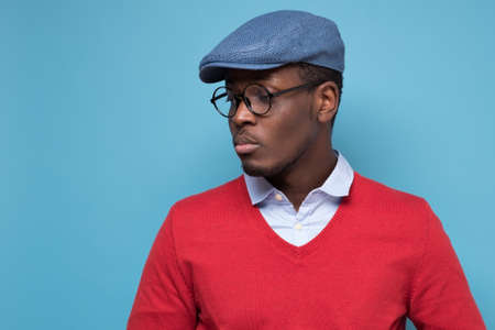 Handsome african young man in blue cao and glasses thinking looking aside. Hard decision concept. Stock fotó