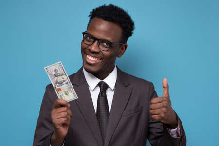 Young african man in suit holding dollars with big smile doing thumb up with finger. Studio shot on blue wall.