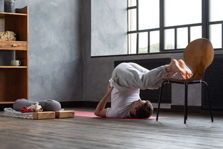 halasana plough pose by caucasian man working out at home.