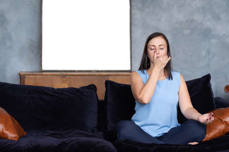 Young caucasian woman working out in living room breathing Pranayama