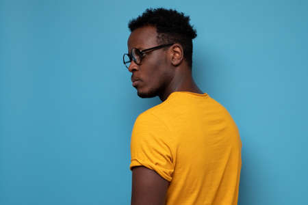 African man in glasses turning back. He is standing alone Stock Photo