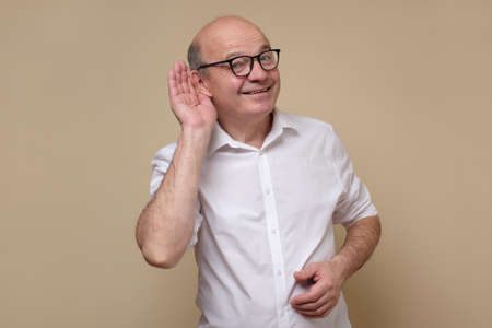 Senior bald male adult in glasses listening carefully, spying, being curious