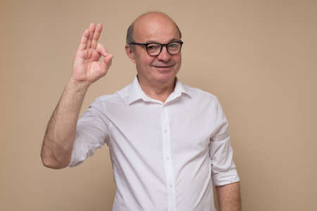 Happy mature bald man in glasses doing ok gesture.