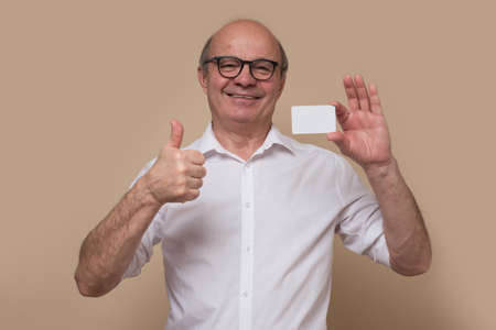 Satisfied senior man holding and showing blank card ready for your text