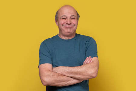 Elderly caucasian man barely holding back laughter, puffing out his cheeks