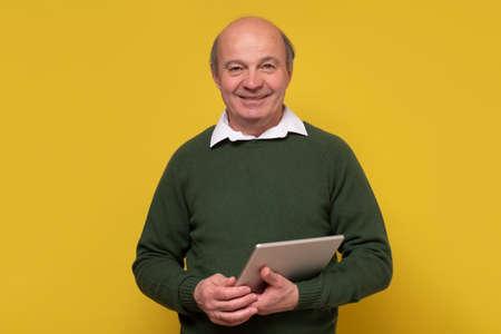 Elegant senior bald man smiling confident at camera holding a tablet