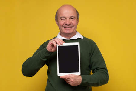 Senior aged middle aged man holding tablet with blank screen