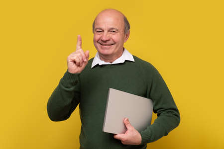 Smiling senior man holding alaptop pointing up