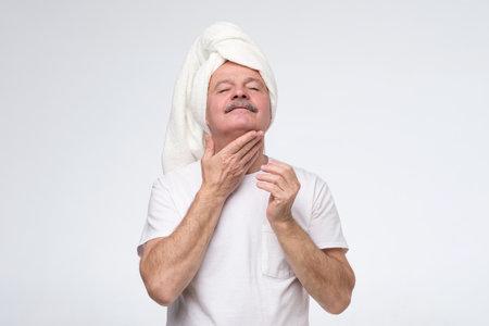 Mature man using cream for face skin
