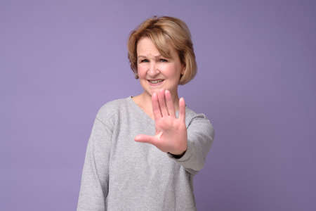 Middle age woman doing stop sing with palm of the hand showing five fingers.