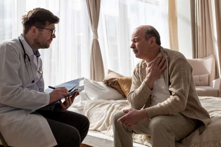Doctor listening to elderly man complaints visiting him at home