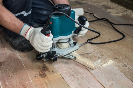 router: Using an electric router for cutting wooden boards