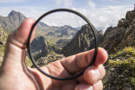 camera lens: Hand puts a transparent clean protective UV filter to the camera, in the background a beautiful landscape and mountains Stock Photo