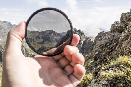 Hand puts a polarization filter to the camera, in the background a beautiful landscape and mountains