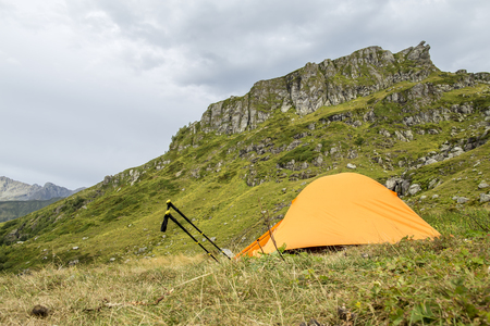 trekking pole: Orange tent in the mountains and trekking pole like a snail crawling