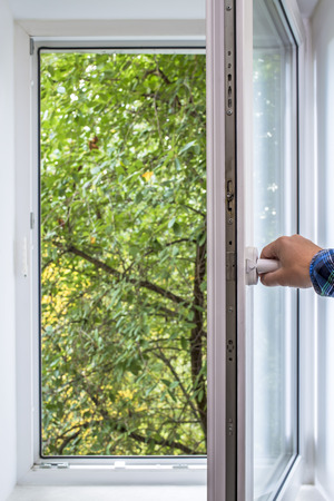 man opens pvc window, which you can see green of a tree park in the ecologically clean area of the city with fresh air Stock Photo