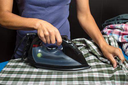 steam iron: woman in a blue T-shirt ironing plaid shirt and other clothing using black iron on a dark background