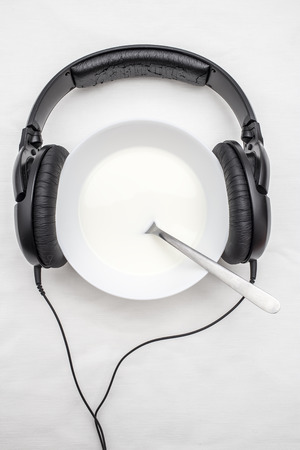 to partake: wearing headphones on a plate with a spoon position inside, symbolizing musical taste