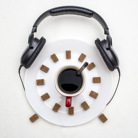 taza: Concept of morning coffee as an alarm clock, arrow are made of plates and cups, and the dial is made of pieces of sugar, above are headphones