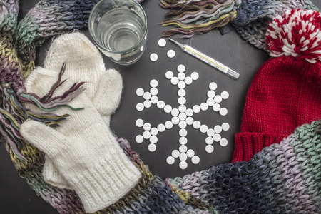 concept snowflakes made from medicinal tablets, lie close colorful winter clothes, a glass of water and a thermometer.