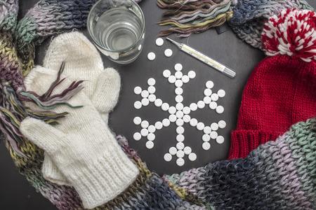 acqua bicchiere: fiocchi di neve concetto base di compresse medicinali, si trovano stretti vestiti invernali colorati, un bicchiere d'acqua e un termometro. Archivio Fotografico