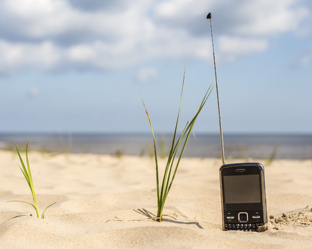 mobile communication: phone with buttons and a very long antenna receives a signal on a sandy beach
