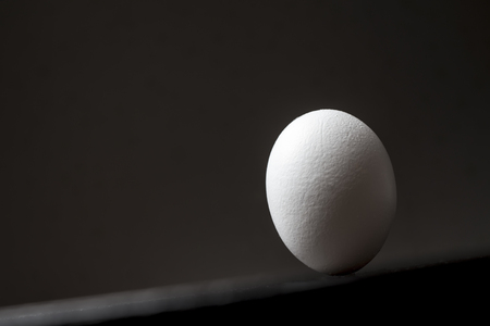friction: the egg is stable upside down on a wooden tilted table against a dark background and is not rolling