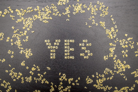 The answer yes made up of a set of words no, with small pasta letters on a dark background wooden board surrounded by other letters of the alphabet, demonstrating the hidden meaning Stock Photo