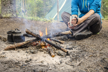 heated: Girl in a blue jacket sitting while camping near the bonfire close to tent is heated and drink hot tea