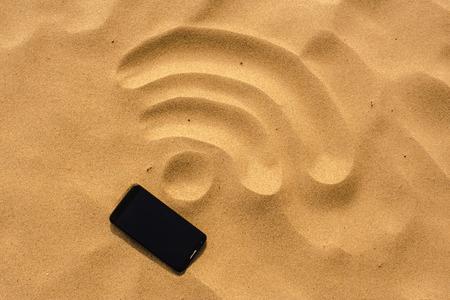 telefone celular deitado na praia, na areia, que esbo Imagens