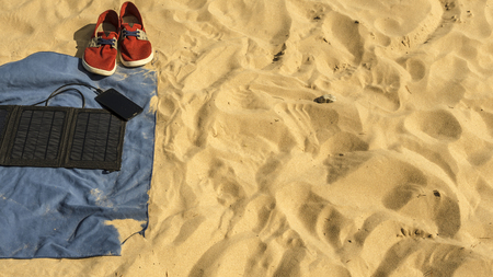 in the sand on the beach are: blue towel, red sneakers, a phone that is charged from a portable solar panel battery.