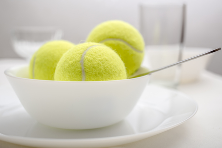 Tennis balls are in a bowl instead of ice cream, symbolizing changes and refusal of desserts and sweet and replacement of sports and healthy lifestyle. White variant.